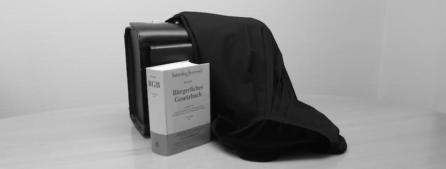 Gesetzbuch, Aktentasche und Robe